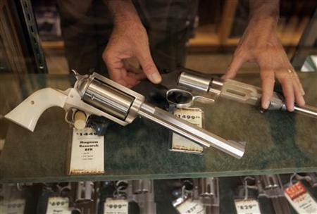 A salesman takes a gun out of the display case at a store in Fort Worth, Texas June 26, 2008. REUTERS/Jessica Rinaldi