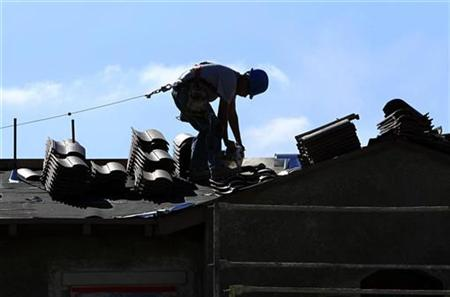 A construction worker cuts tiles as he installs a roof on a home in a new subdivision being built in San Marcos, California April 23, 2010. REUTERS/Mike Blake