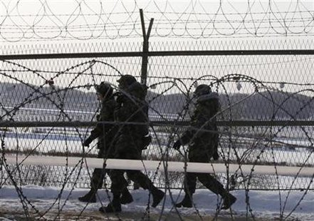 South Korean soldiers patrol along military fence near the demilitarized zone separating the two Koreas in Paju, about 50 km (31 miles) north of Seoul January 12, 2010. REUTERS/Lee Jae-Won