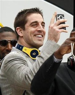 Green Bay Packers quarterback Aaron Rodgers videotapes his arrival for Super Bowl XLV at DFW airport in Dallas, Texas January 31, 2011. REUTERS/Jeff Haynes