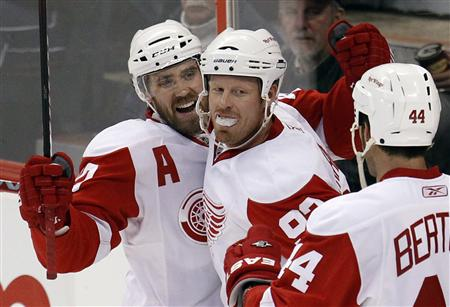 Detroit Red Wings Johan Franzen (C) celebrates his fourth goal against the Ottawa Senators with teammates Henrik Zetterberg (L) and Todd Bertuzzi during the third period of their NHL hockey game in Ottawa February 2, 2011 REUTERS/Chris Wattie