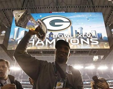 Green Bay Packers cornerback Charles Woodson carries the Vince Lombardi championship trophy off the field after defeating the Pittsburgh Steelers in the NFL's Super Bowl XLV football game in Arlington, Texas, February 6, 2011. REUTERS/Pierre Ducharme
