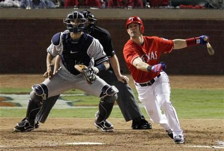 Texas Rangers Michael Young watches his 2 RBI double with New York Yankees Jorge Posada (L) during the fourth inning in Game 1 of their Major League Baseball ALCS playoff series in Arlington, Texas, October 15, 2010. REUTERS/Tim Sharp