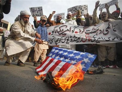 "A man burns a mock U.S. flag during a rally to protest against U.S. special forces officer Raymond Davis in Lahore February 24, 2011. The placards and banner read,"" Hang killer U.S. spy Raymond Davis"". REUTERS/Mohsin Raza"
