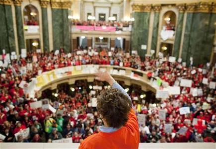 A member of the State Assembly Democrats waves as supporters cheer after the party spoke in the Assembly to voice their opinion against the proposed bill by Republican Governor Scott Walker in Madison, Wisconsin, February 18, 2011. REUTERS/Darren Hauck