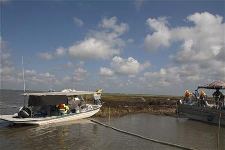 Workers use long poles to mop up oil from the Deepwater Horizon oil spill in a marsh near Cocodrie, Louisiana in this July 15, 2010 file photo. REUTERS/Lee Celano