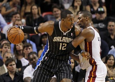 Orlando Magic center Dwight Howard (L) tries to battle past Miami Heat forward Chris Bosh during their NBA basketball game in Miami, Florida March 3, 2011. REUTERS/Joe Skipper