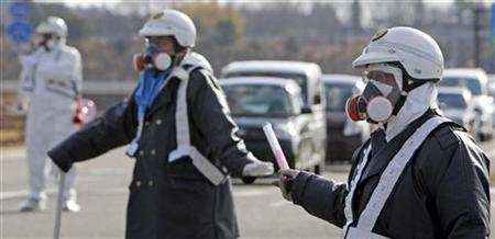 Police officers wearing respirators guide people to evacuate away from the Fukushima Daiichi nuclear plant following an evacuation order for residents who live in within a 10 km (6.3 miles) radius from the plant after an explosion in Tomioka Town in Fukushima Prefecture March 12, 2011. REUTERS/Asahi Shimbun