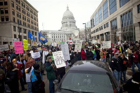 Demonstrators march around the State Capitol building as they protest against the proposed budget cuts from Wisconsin Governor Scott Walker, in Madison February 25, 2011. Credit: REUTERS/Darren Hauck