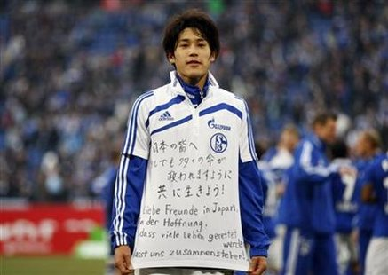 "Schalke 04's Atsuto Uchida poses with a jersey after their German Bundesliga soccer match win against Eintracht Frankfurt in Gelsenkirchen March 12, 2011. The words read, ""Dear friends in Japan, in the hope that many lives are saved, let us stand together!"". REUTERS/Ina Fassbender"