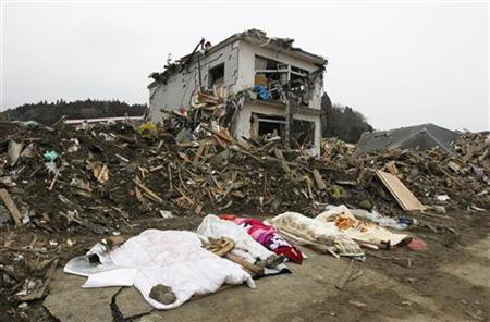 The bodies of victims are covered by blankets at a village destroyed by the earthquake and tsunami in Rikuzentakata in Iwate prefecture, northeast Japan March 15, 2011. REUTERS/Lee Jae-Won
