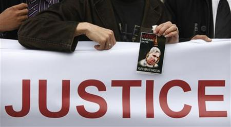 A man holds an image of U.S. national Raymond Davis during a rally against Davis in Islamabad February 28, 2011. REUTERS/Faisal Mahmood