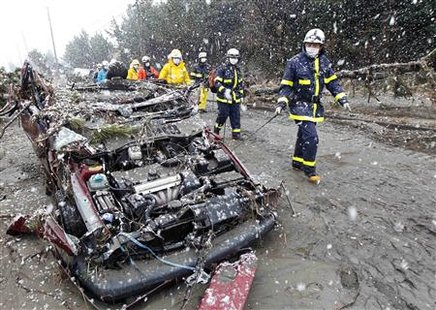 Rescue workers walk past a destroyed car during heavy snowfall at a factory area devastated by an earthquake and tsunami in Sendai, northern Japan March 16, 2011. REUTERS/Kim Kyung-Hoon