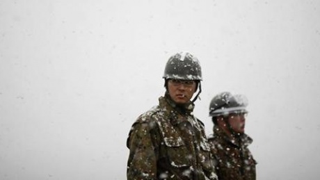 Heavy snow falls as members of the Japan Self-Defense Force arrive at the devastated residential area in Otsuchi, March 16, 2011. REUTERS/Damir Sagolj