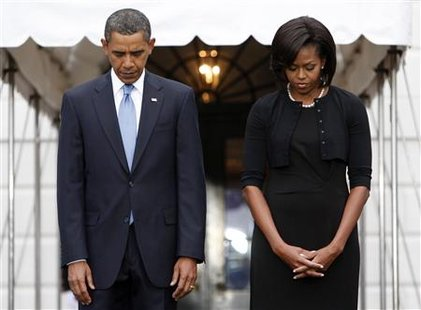 U.S. President Barack Obama and first lady Michelle Obama take part in a moment of silence marking the eighth anniversary of the September 11 attacks on New York, Washington, and Pennsylvania, on the South Lawn at the White House in Washington, September 11, 2009. REUTERS/Jim Young