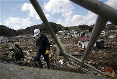 A man walks on a seawall at an area destroyed by the March 11 earthquake and tsunami, in Taro town, Iwate prefecture March 29, 2011. REUTERS/Carlos Barria