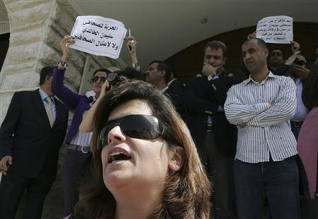 "Lena (C), wife of Reuters correspondent Suleiman al-Khaledi who is missing in Syria, protest with Jordanian journalists outside the Jordan Press Association in Amman March 31, 2011. The placards read: ""Freedom for Suleiman al-Khalidi"". REUTERS/Majed Jaber"