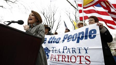 "Activists hold a sign as Congresswoman Michele Bachmann (R-MN) speaks at the Tea Party Patriots ""Continuing Revolution"" rally on Capitol Hill in Washington March 31, 2011. REUTERS/Kevin Lamarque"
