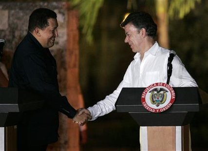 Colombia's president Juan Manuel Santos (R) and his Venezuelan counterpart Hugo Chavez shake hands during a news conference in Cartagena April 9, 2011. REUTERS/Jairo Castilla