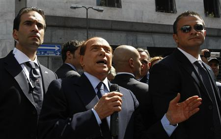 Italian Prime Minister Silvio Berlusconi gestures as he speaks to supporters outside Milan's court April 11, 2011. REUTERS/Alessandro Garofalo