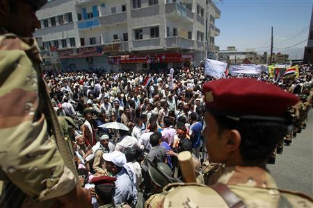 Army soldiers stand guard at a barrier blocking the way of demonstrators as they demand the ouster of Yemen's President Ali Abdullah Saleh in the southern city of Taiz April 17, 2011. REUTERS/Khaled Abdullah