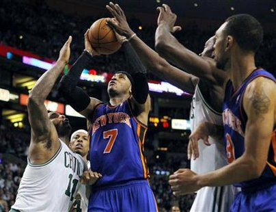 New York Knicks forward Carmelo Anthony (7) drives to the basket between Boston Celtics forward Glen Davis (L) and forward Kevin Garnett as Knicks forward Jared Jeffries (R) looks on during the second half of Game 2 of their NBA Eastern Conference playoff series in Boston, Massachusetts April 19, 2011. REUTERS/Brian Snyder