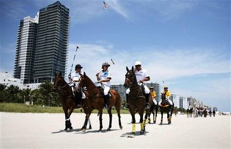 (L-R) AMG-Mercedes polo players Michael Liss, Nacho Figueras and Pelon Escapite ride along Miami Beach en route to their first round match in this 2010 handout image. REUTERS/Mitchell Zachs-The Polo Life/Handout