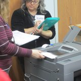An election official puts a ballot through a counting machine during Marathon County's recount of Wisconsin's Supreme Court race