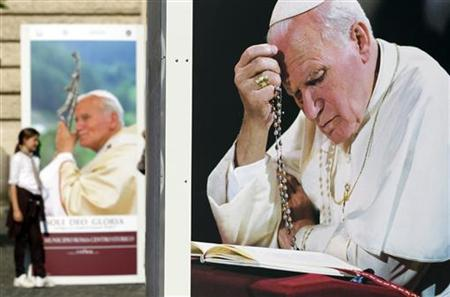 A girl (L) poses next to a picture of Pope John Paul II during an exhibition by the city of Rome in downtown Rome April 20, 2011. REUTERS/Alessandro Bianchi