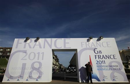 A man gestures for a souvenir photo next to at the entrance of the venue of the G8 summit in Deauville, northern France, May 24, 2011. The leaders of the G8 countries will be meeting in Deauville on May 26-27. REUTERS/Andrew Winning