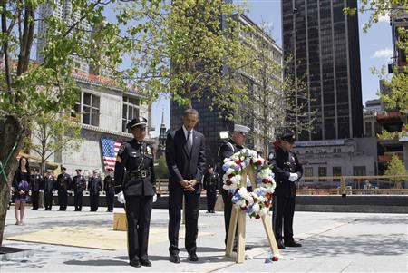 President Barack Obama observes a moment of silence during a wreath laying ceremony at the National September 11th Memorial with New York City police officers and firefighters at the World Trade Center site in New York, May 5, 2011. REUTERS/Brendan McDermid