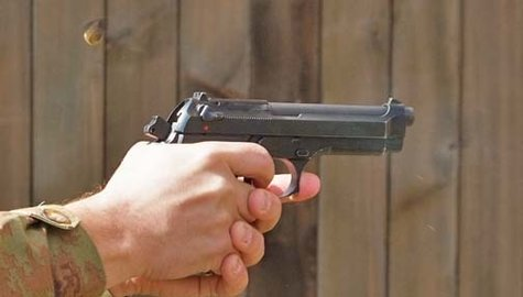 A handgun being fired at a firing range.