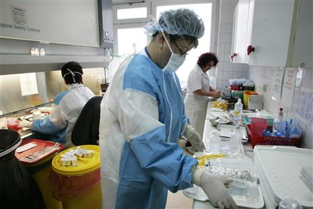 "Healthcare workers prepare medicine at the Cancer Center and Institute of Oncology in Warsaw in this February 8, 2007 file photo. The clinical trials business has gone global as drugmakers seek cheaper venues for studies and cast their net further afield for big pools of ""treatment-naive"" patients who are not already taking other drugs that could make them unsuitable subjects for testing new ones. And it is not only the practicalities"