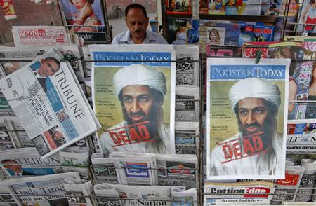 A roadside vendor sells newspapers with headlines about the death of al-Qaeda leader Osama bin Laden, in Lahore in this May 3, 2011 file photograph. REUTERS/Mohsin Raza/Files