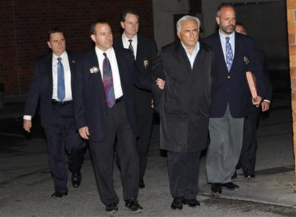 Dominique Strauss-Kahn (2nd R), head of the International Monetary Fund (IMF), departs a New York Police Department precinct late May 15, 2011. REUTERS/Mike Segar