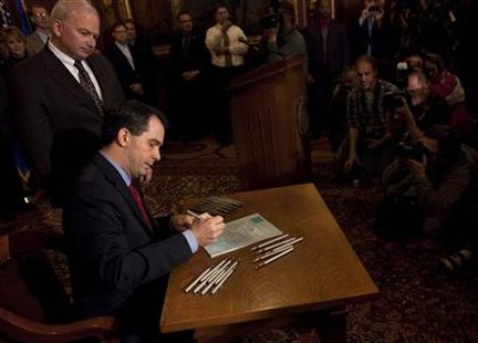 Wisconsin State Governor Scott Walker signs the ceremonial bill, following an elimination of almost all collective bargaining for most public workers by the Republican controlled House and Senate, at the state Capitol in Madison, Wisconsin March 11, 2011. REUTERS/Darren Hauck