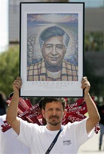 A man holds a photo of Cesar Chavez, the founder of the United Farm Workers, during an immigration rights rally at the Arizona State Capital in Phoenix, Arizona, September 4, 2006. REUTERS/Jeff Topping