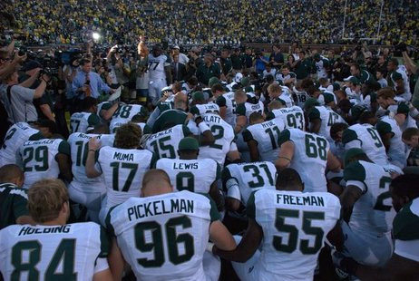 Michigan State Football prays following their 2010 victory over Michigan.
