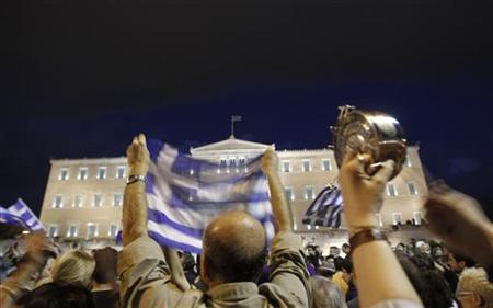 A protester hits a pot during a protest rally against a new austerity package in front of the parliament building in Athens