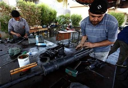 Libyan volunteers fix jammed weapons captured from Muammar Gaddafi forces at a workshop in Misrata