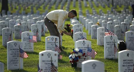 A relative of a buried serviceman places flowers at his headstone in Section 60 of Arlington National Cemetery