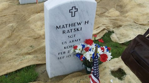 Patriotic flowers are set against the tombstone of Korean War vet Matt Ratski at the Great Lakes National Cemetery in Holly, MI on May 29, 2011