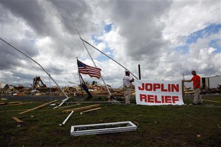 Volunteers hang a sign at a church, which is destroyed by a tornado in Joplin, Missouri