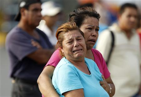 Relatives of a slain man react at the crime scene in Monterrey