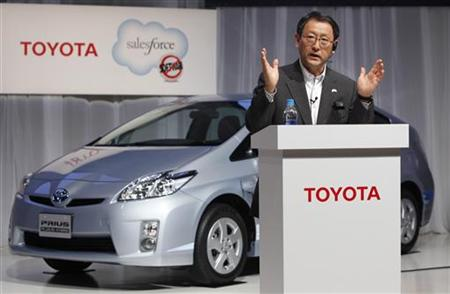 Japan's Toyota Motor Corp President Toyoda speaks next to a Prius plug-in hybrid during a news conference in Tokyo