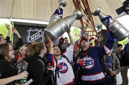 Hockey fans celebrate the return of NHL hockey during a rally in Winnipeg