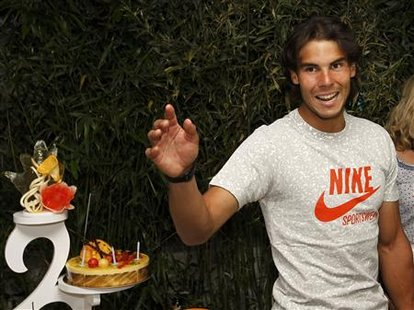 Rafael Nadal of Spain waves after posing for the media with his birthday cake during the French Open tennis tournament at Roland Garros in P