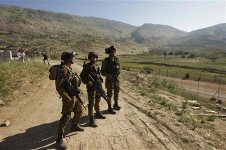 Israeli soldiers stand guard on the Israeli-Syrian border near Majdal Shams in the Golan Heights