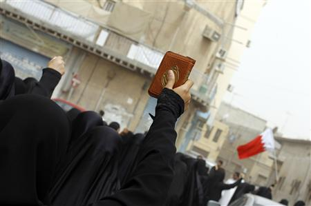 Female anti-government protester holds up a Koran during a march to demand the end of the regime on the streets of Sanabis in Manama