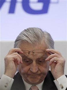 ECB Governor Trichet adjusts his glasses during a conference in Madrid on reforms of the financial system